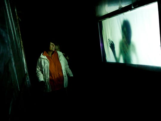 Coretta Krozek, of Warren, looks over at a video projection of a woman being murdered as she walks with a group Oct. 11 at Dark House Haunted Mansion near Brown City.