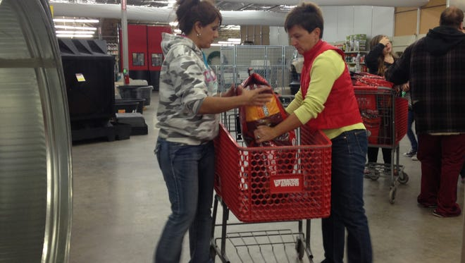 Volunteers help load dog food into a cart during the C-PAWS Pet Food Assistance Program event at the Carlsbad Tractor Supply Saturday.