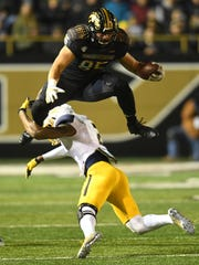 Western Michigan Broncos tight end Donnie Ernsberger (85) jumps over Toledo Rockets defensive back Jordan Martin (2) during the first half at Waldo Stadium.