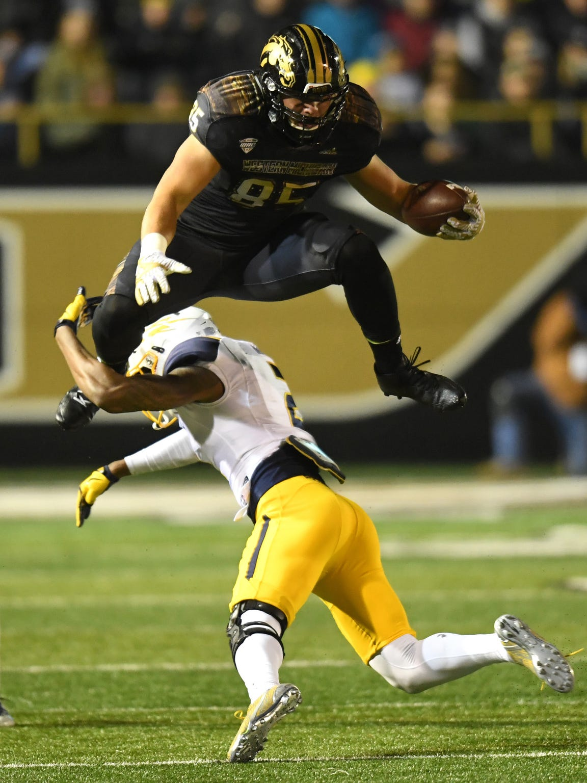 Western Michigan tight end Donnie Ernsberger jumps over Toledo defensive back Jordan Martin.