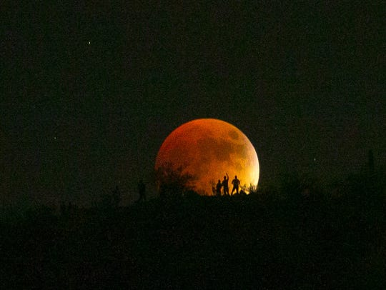 "Hikers look at the ""Super Blood Moon"" seen from the"