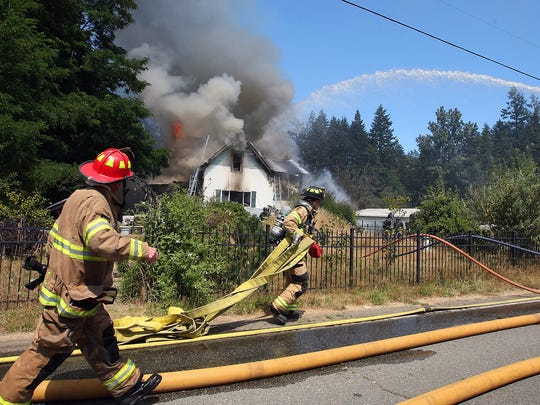 Bremerton Fire Department's Lt. Rex Hinkle (left) and firefighter Benny Cammarata (center) pull firehose to the scene as crews battle a two-alarm house fire on Goldenrod Street in Port Orchard on Friday.