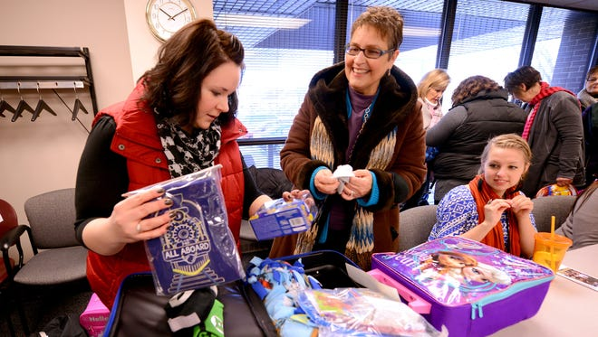 CASA of Brown County put together overnight bags containing comfort items for children who are removed from homes by Child Protective Services staff. Supervisor Lauren Krukowski, left, looks over the contents with Connie Greenawald, executive director of CASA in the Sophie Beaumont Building in downtown Green Bay on Dec. 19.