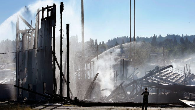 A firefighter stops to take a photo of the smoldering remains of Civic Stadium, Tuesday, June 30, 2015, in Eugene, Ore. A fire destroyed Eugene's historic Civic Stadium on Monday evening and prompted the temporary evacuation of a two-block area, the fire chief said. The stadium was approved by voters in 1938 during the Great Depression and opened that same year. (Chris Pietsch/The Register-Guard via AP)