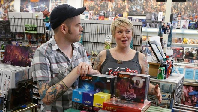 Patrick Titus and Sarah Titus are shown at their store, The Comic Book Shop in Brandywine Hundred, on Thursday. Printed comic books still have a strong fan base.