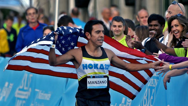 Leo Manzano celebrated with fans along the finish line after he won the men's road championship race with a time of 4:05.71 at the Drake Relays Grand Blue Mile in downtown Des Moines on Tuesday evening April 22, 2014.