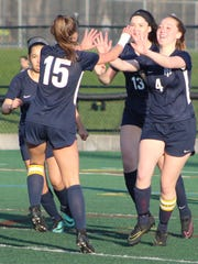 Farmington senior Erin Abramczyk (4) celebrates the game's first goal against Seaholm with teammates Kristina Agee (2), Marlee Pope (15) and Casey Borden (13).