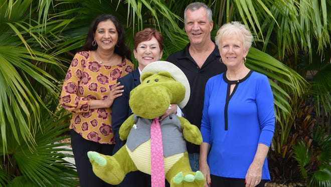 """Event committee members, from left, Naheed Shareef, Debbie Butler, with special mascot """"Gus,"""" co-chair Mike Henry, Guild president, and Beverley Sarlo are pictured at the PGA Island Club getting ready for an event to benefit abused children. """"An Evening for Sanctuary4Kids"""" is at 6 p.m. Nov. 11 at PGA Island Club."""