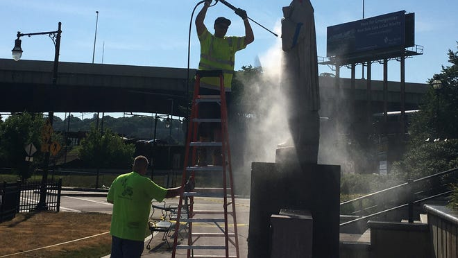A silhouette of workers as they power wash the Christopher Columbus statue on June 23 in front of Union Station. It was vandalized with red paint overnight.
