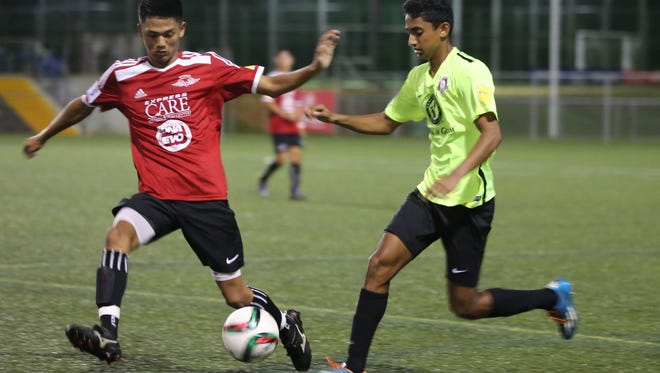 Wings Red's Jordan Jasmin attempts to stop Bank of Guam Strykers' Alan Thomas from advancing with the ball near the touchline during an Aloha Maid Minetgot Cup Elite Youth League during a U17 match at the Guam Football Association National Training Center Wednesday. Wings Red won 2-0.
