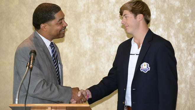 Independence Bowl Chairman Paul Pratt (left) congratulates Sam Burns after awarding the area golfer the 2014 Carl Mikovich Sportsman of the Year Award during a ceremony at the East Ridge Country Club October 7, 2014.