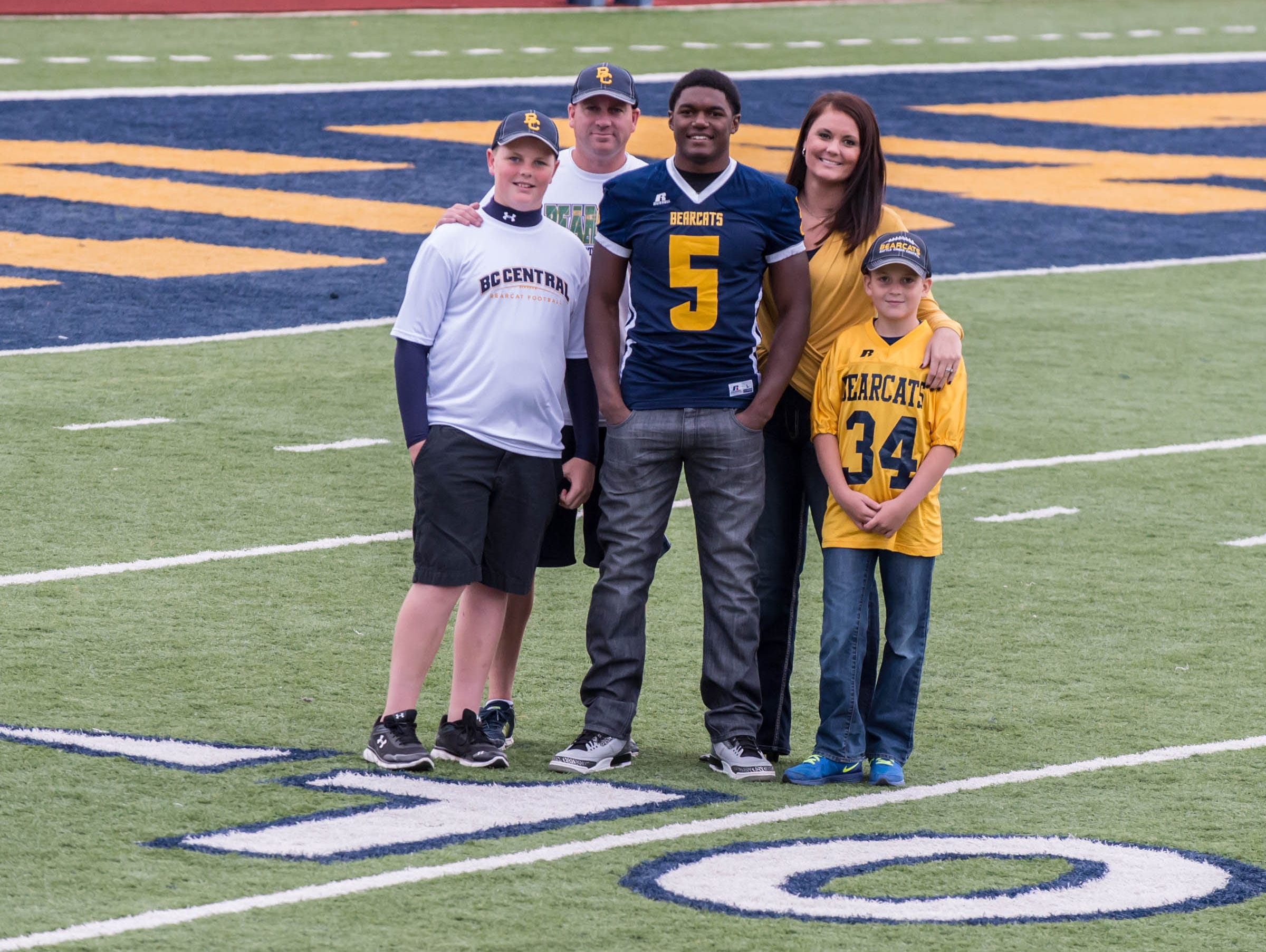 Battle Creek Central football standout Brandon Randle, with his surrogate family - BCC head coach Lorin Granger, his wife Audra Granger, Kyler Granger and Kayden Granger.