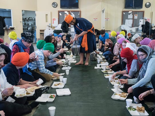 Sikh community members serve lunch to the students. The meal is traditionally served before worship services begin.