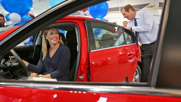 Courtney Rice, left, sits in the driver's seat of her new 2015 Chevrolet Cruze as Andy Mohr, right, CEO of Andy Mohr Automotive, puts her children in the back seat, at the Plainfield business, Monday, June 29, 2015.