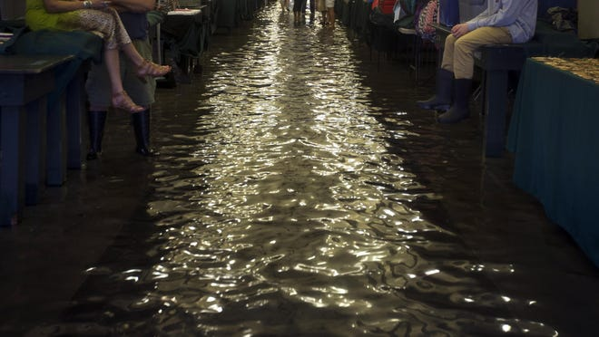In this Thursday, Oct. 1, 2015 photo, visitors seek refuge by sitting on the tables of Charleston's City Market during a heavy rainfall in Charleston, S.C. Like most things Charleston, understanding the problem is to understand the city's past. Over the years, the peninsula that juts out toward the Atlantic Ocean has largely expanded by filling in creeks and marshes, leaving the streets susceptible to flooding because the water has nowhere else to go. (AP Photo/Stephen B. Morton)