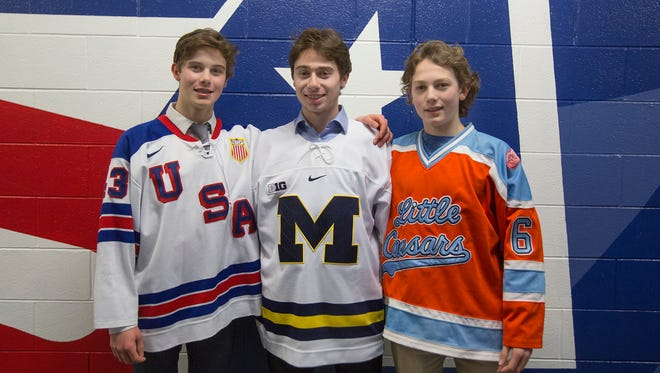 The Hughes brothers pose in their respective hockey jerseys at USA Hockey Arena in Plymouth on Sunday. Forward Jack Huges (left) plays for USA Hockey's National Team Development Program. Quinn Hughes (center) is a freshman defenseman for the Michigan Wolverines. Luke Hughes (right) is a defenseman for Detroit Little Caesars.