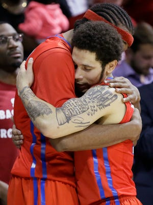 SMU seniors guard Nic Moore (11) hugs teammate Sterling Brown during the second half of an NCAA college basketball game against Connecticut, March 3, 2016, in Dallas. SMU won 80-54.