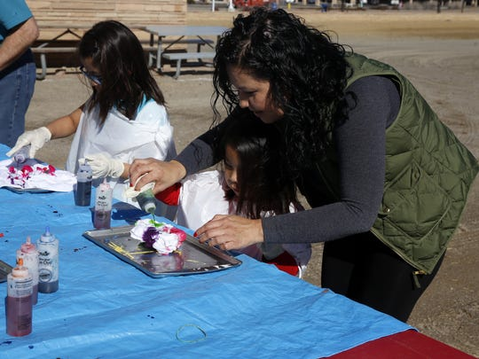 Lana Tsosie helps her niece Alyssa Armstrong, 4, tie dye a shirt Saturday while her other niece Aiyanna Armstrong, 10, works on a shirt of her own at the Farmington Museum at Gateway Park.