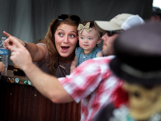 Janet Kendall (left) and Brandon Burnsed (right) point out a passing barge for one-year-old Birdy Burnsed while visiting friends at the VoodooQ booth on the final day of the annual Memphis in May World Championship Barbecue Cooking Contest at Tom Lee Park Saturday.