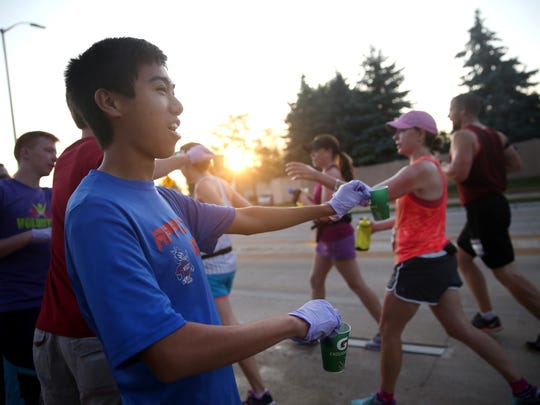 Kenny Mui, a volunteer with Community First Fox Cities Marathon, hands out Gatorade at the first water station in Appleton.