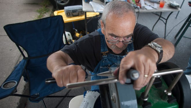 Neil Jacob sharpens a knife for a customer at the Collingswood Farmers' Market.
