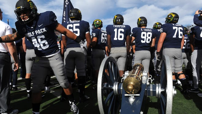 Nevada players stand with the Fremont Cannon before taking on UNLV at Mackay Stadium.
