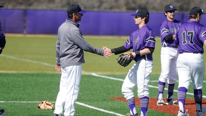 Wylie coach Clay Martin, left, shakes hands with Gatlin Martin (21) following the Bulldogs' 7-5 victory against Ranger Junior College at Bulldog Field on Thursday, March 1, 2018.