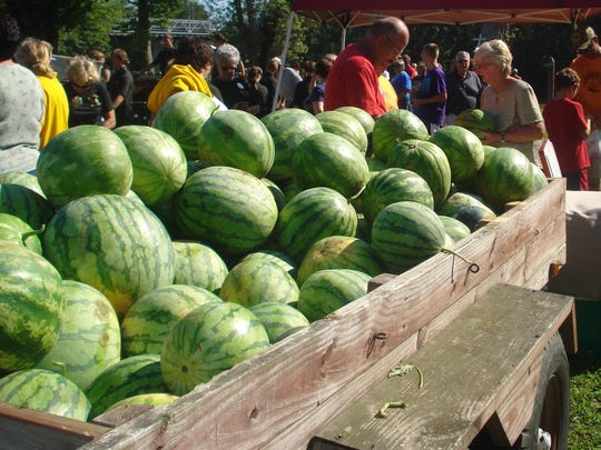 Patrons glance at a cart of melons on sale from Miller's Melons at a previous Dresden Melon Festival.