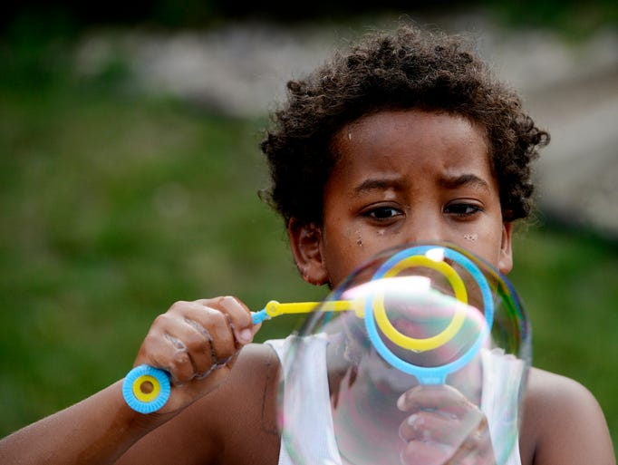 Darrious Franklin, 7, blows bubbles while participating in Superhero Vacation Bible School at Church of the Good Shepherd Wednesday night, July 9, 2014.
