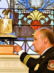 York City Assistant Chief Patrick Rose rings the bell