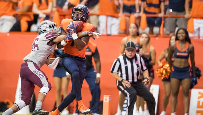 Amba Etta-Tawo #7 of the Syracuse Orange pulls in a touchdown reception as Cortney Mimms #26 of the Colgate Raiders defends.