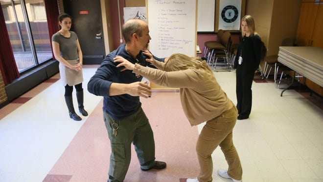 Michael Nilsson (center left) and Therese Hahn (center right), nurses at the Milwaukee County Mental Health Complex, train medical students from the Medical College of Wisconsin, Alexandra Neiman (left rear) and Caitlin Moore (right rear) how to handle an attack from a patient.