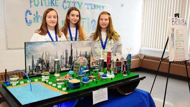 St. Valentine presenters (from left) Anna Damuth, Frankie Nelson-Pawlik and Faith Emmerling with a model representing part of Briviba, a city in the year 2224 that they and fellow eighth-graders researched and designed. St. Valentine's eighth-grade class was the regional winner last month in the Engineering Society of Detroit's Future City competition.