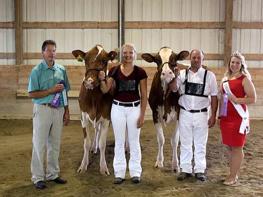 District 8 Grand Champion and Reserve Grand Champion of the Open Show (from left) Judge Mike Deaver, Grand Champion Milgene Big Red Jersey-Red, Ari Hildebrandt, Reserve Grand Champion Poercrest Adon Popsicle-Red exhibited by Mason Dairy Farm, LLC, Matt Smith, 2017 WHA Princess Attendant Kelsey Cramer.
