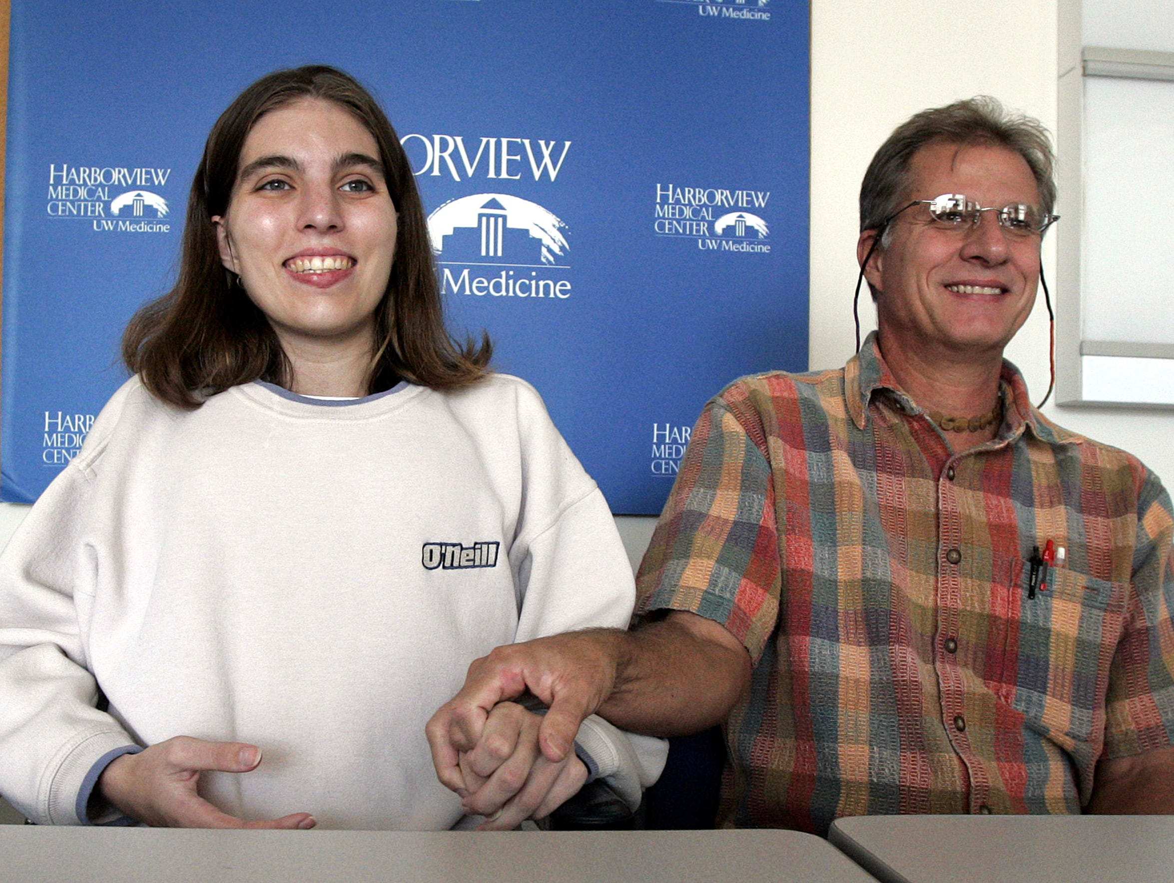 Vernon Bush, right, reaches out to take the hand of his daughter, Layla Bush, following a news conference Sept. 12, 2006, at Seattle's Harborview Medical Center. Bush had been wounded two months earlier in a mass shooting at the Jewish Federation of Greater Seattle. In the podcast Aftermath, Bush describes the trauma endured by her loved ones, including her father, following her shooting.