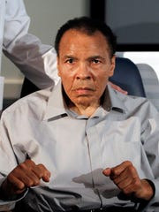 In this Feb. 22, 2012, file photo, former heavyweight boxing champion Muhammad Ali displays his signature boxing pose after honoring outstanding surgeons and physicians at St. Joseph's Hospital Barrow Neurological Institute in Phoenix.  Ali, the magnificent heavyweight champion whose fast fists and irrepressible personality transcended sports and captivated the world, has died according to a statement released by his family Friday, June 3, 2016. He was 74.