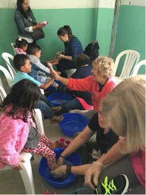 Volunteers wash childrens' feet in Soacha, Colombia. The Good Samaritan Society – Las Cruces Village will host a posole luncheon Thursday to help fund an upcoming Colombia Mission.