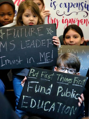 Students holds up rally signs, joining several hundred parents, educators, education activists and a handful of legislators in an education rally at the Capitol in Jackson, Miss., Thursday, March 16, 2017. Advocates for public schools are opposing legislative leaders' plans to rewrite the state's school funding formula.