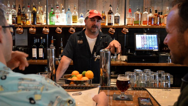 Forgotten Mile Ale House manager, Rich Nofi, talks beer with two new customers.