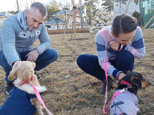 In this undated photo provided by Free Korean Dogs, figure skating coach Bruno Marcotte and his wife, Canadian figure skater Meagan Duhamel, pet their dog Moo-tae, right, and another dog in South Korea. Duhamel already has one life-changing souvenir from South Korea, and it's not a medal. The Olympic pairs skater rescued a puppy from the Korean dog meat trade while competing in Pyeongchang last year, and she's helping organize more adoptions while skating there at this year's games. (EK Park/Free Korean Dogs via AP)