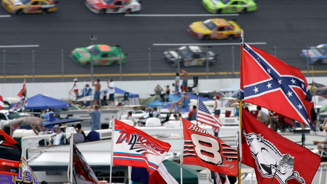 In this Oct. 7, 2007, file photo, a Confederate flag flies in the infield as cars come out of Turn 1 during a NASCAR auto race at Talladega Superspeedway in Talladega, Ala. NASCAR banned the Confederate flag from its races and venues Wednesday, June 10, 2020, formally severing itself from what for many is a symbol of slavery and racism.