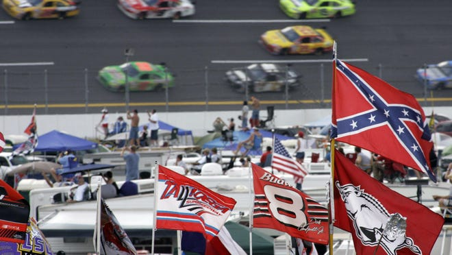 A Confederate flag flies in the infield as cars come out of Turn 1 during a NASCAR race Oct. 7, 2007 at Talladega Superspeedway in Talladega, Ala. NASCAR banned the Confederate flag from its races and venues Wednesday, June 10. formally severing itself from what for many is a symbol of slavery and racism.