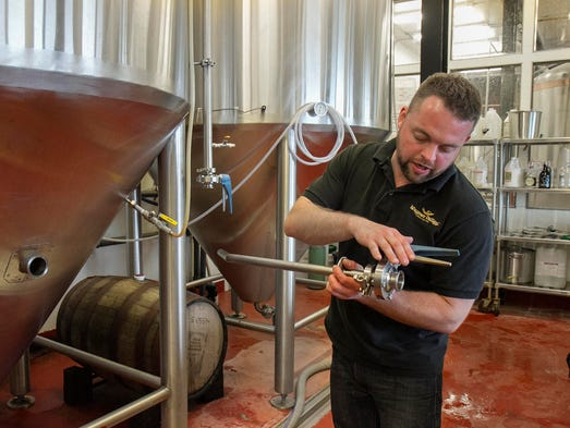 Brent Wojnowski, Wagner Valley Brewing Co. brewmaster, describes how a rotating racking arm allows the brewmaster to drain a beer tank without drawing sediment that has settled to the bottom.