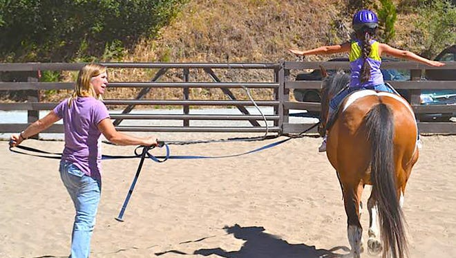 Hope, Horses & Kids founder and executive director Lori Tuttle works with a Peacock Acres foster child during their life and horsemanship skills program.
