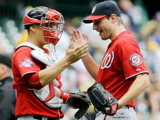Washington Nationals starting pitcher Max Scherzer is congratulated by catcher Jose Lobaton after a baseball game against the Milwaukee Brewers Sunday, June 14, 2015, in Milwaukee. Scherzer threw a complete game one-hitter as the Nationals won 4-0. (AP Photo/Morry Gash)
