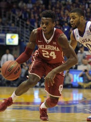 Oklahoma guard Buddy Hield (24) moves the ball against
