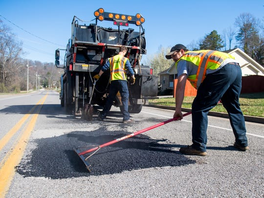 A crew patches a pothole on Bradshaw Road in front of Victor Ashe Park on Tuesday, February 27, 2018.