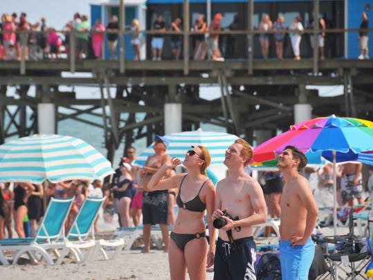 People on the beach north of the Cocoa Beach Pier watch