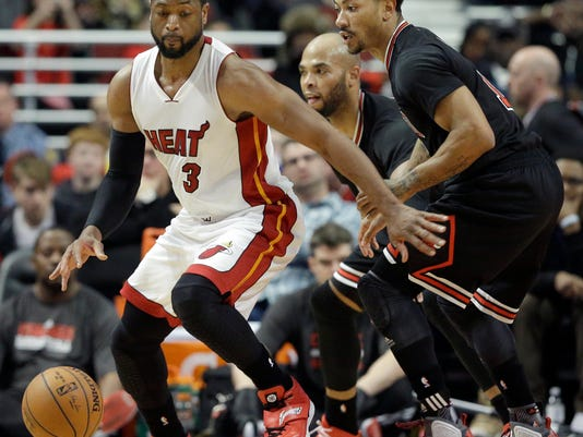 Miami Heat guard Dwyane Wade (3) controls the ball against Chicago Bulls guard Derrick Rose (1) during the second half of an NBA basketball game in Chicago, Sunday, Jan. 25, 2015. The Heat won 96-84. (AP Photo/Nam Y. Huh)