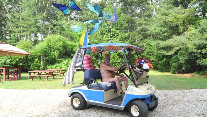 """Sean Maloney wears only a mask and work boots as he drives his decorated golf cart around Sandy Terraces, a nudist campground in Marstons Mills. """"The hardest thing here right now is not to be able to shake hands or hug,"""" he said of coronavirus-related social distancing rules."""